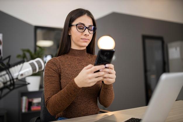 Vrouw in een radiostudio met smartphone en microfoon