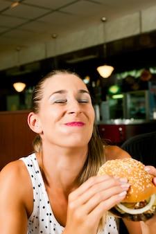 Vrouw in een restaurant dat hamburger eet