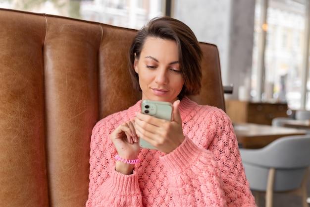 Vrouw in een restaurant in een warme trui kijkt naar iets aan de telefoon