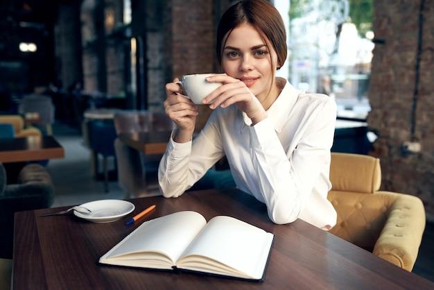 Vrouw in een restaurant met een notitieblok op tafel en een kopje in de hand