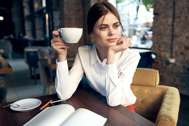 Vrouw in een restaurant met een notitieblok op tafel