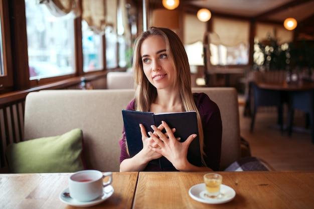 Vrouw in een restaurant met menu in handen