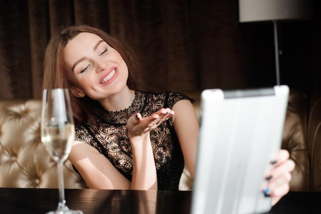 Vrouw in een restaurant ontspannen met een glas champagne en tablet pc.