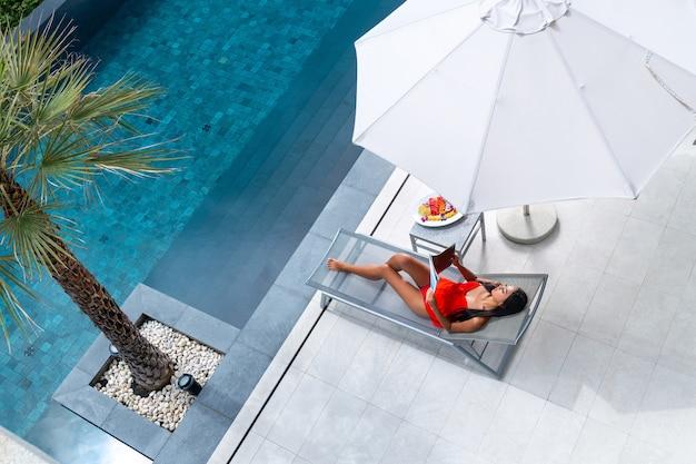 Vrouw in een rode bikini die op een zonnebank rust en een tijdschrift leest