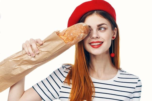 Vrouw in een rode hoed met een frans brood in haar handen een gastronomische snack-levensstijl