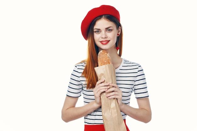 Vrouw in een rode hoed met een frans brood in haar handen een snack gastronomische levensstijl. hoge kwaliteit foto
