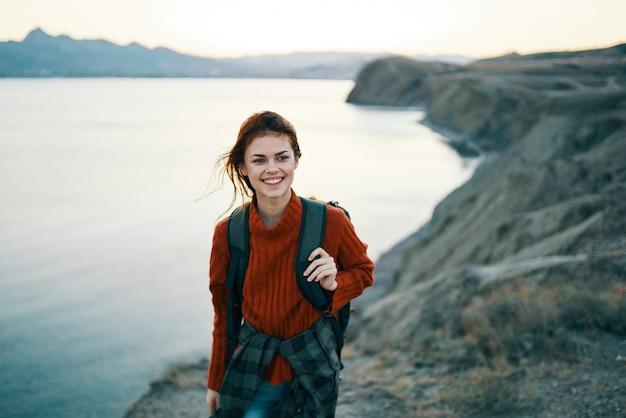 Vrouw in een rode trui buiten in de bergen frisse lucht zee bergen landschap