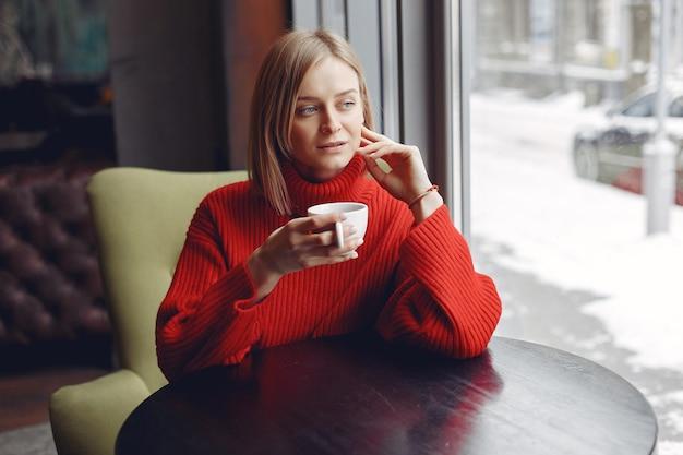 Vrouw in een rode trui. dame drinkt een kop koffie.