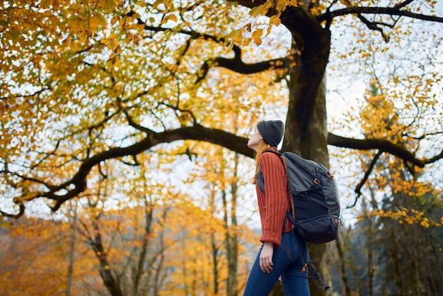 Vrouw in een rode trui met een rugzak loopt 's middags in een herfstpark in de natuur