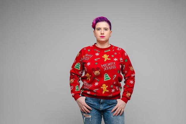 Vrouw in een rode vakantiesweater en gescheurde spijkerbroek met gekleurd haar dat haar duimen in zakken verbergt. nieuwjaar concept