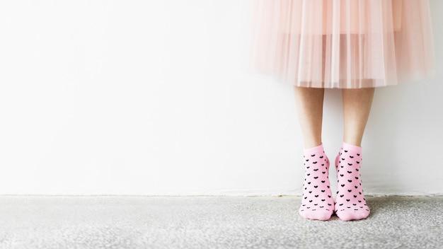Vrouw in een rok die roze sokkenbehang draagt