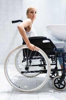 Vrouw in een rolstoel met haar handen op het stuur