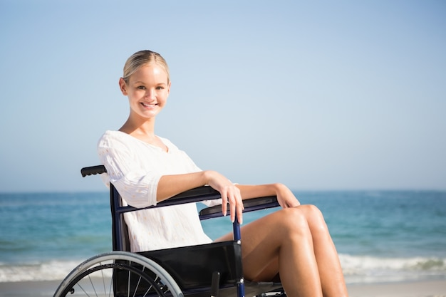 Vrouw in een rolstoel ontspannen op het strand