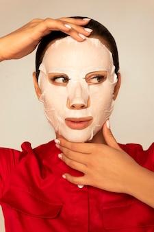 Vrouw in een rood medisch pak op een hydraterend gezichtsmasker.