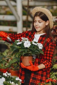 Vrouw in een rood overhemd. werknemer met flowerpoots. dochter met planten