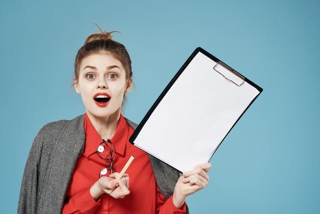 Vrouw in een rood shirt met een jas heeft een vel papier kopieerruimte blauwe achtergrond