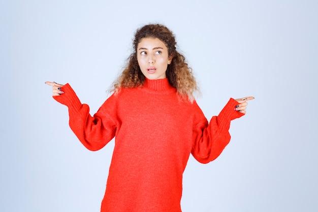Vrouw in een rood sweatshirt dat naar verschillende kanten wijst.