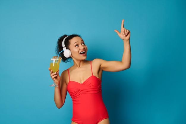 Vrouw in een rood zwempak en hoofdtelefoons die bij een cocktail in haar hand op blauwe achtergrond houden