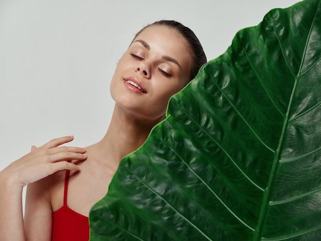 Vrouw in een rood zwempak met gesloten ogen leunde met haar gezicht op een groen blad van een palmboom op een