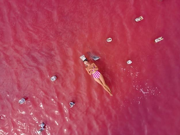 Vrouw in een roze badpak ligt in de zomer op een verwoeste houten brug midden in een roze meer