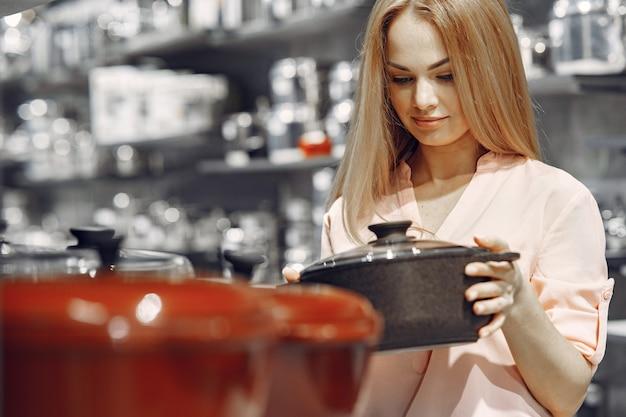 Vrouw in een roze blouse koopt gerechten in de winkel