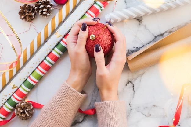 Vrouw in een roze gebreide trui houdt een rode glanzende kerstbal
