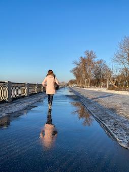 Vrouw in een roze jas loopt langs de dijk in de verte op een heldere dag en wordt weerspiegeld in plassen. verticale oriëntatie