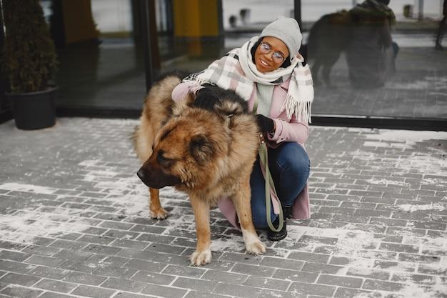 Vrouw in een roze jas met honden