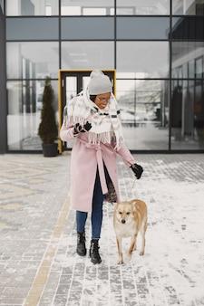 Vrouw in een roze jas, wandelende hond