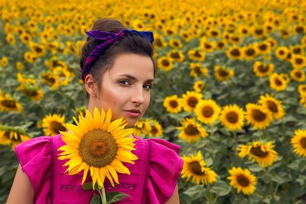 Vrouw in een roze jurk die zich in het veld bevindt en een zonnebloem vasthoudt