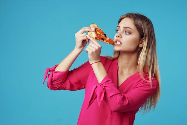 Vrouw in een roze shirt met pizza in haar handen junkfood close-up. hoge kwaliteit foto