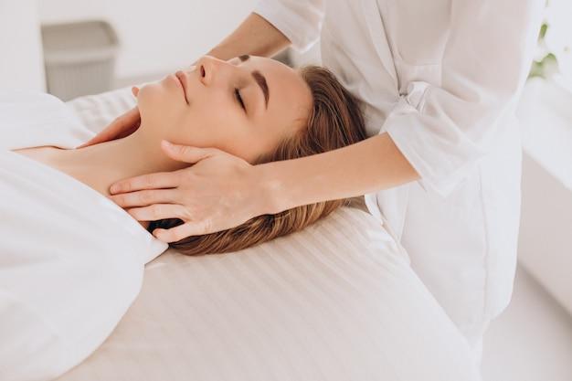 Vrouw in een schoonheidssalon met gezichts- en nekmassage