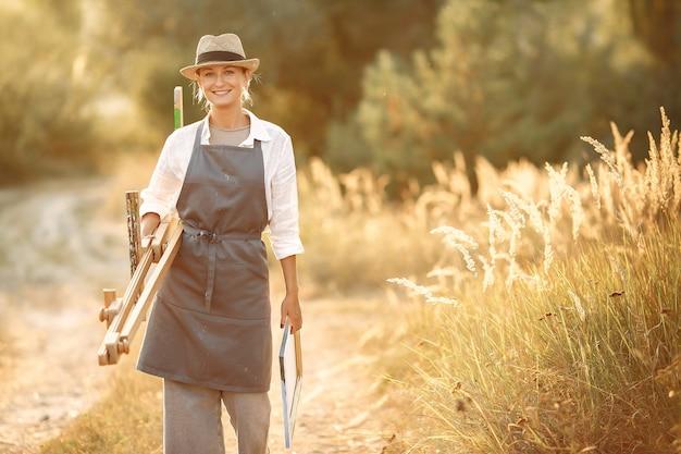 Vrouw in een schort schilderen in een veld