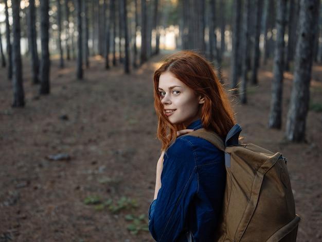 Vrouw in een shirt met een rugzak op haar rug in een dennenbos in de natuur