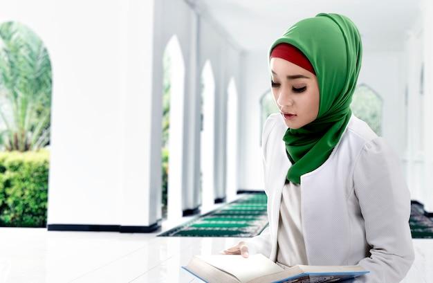 Vrouw in een sluier die de koran op de moskee zit te lezen
