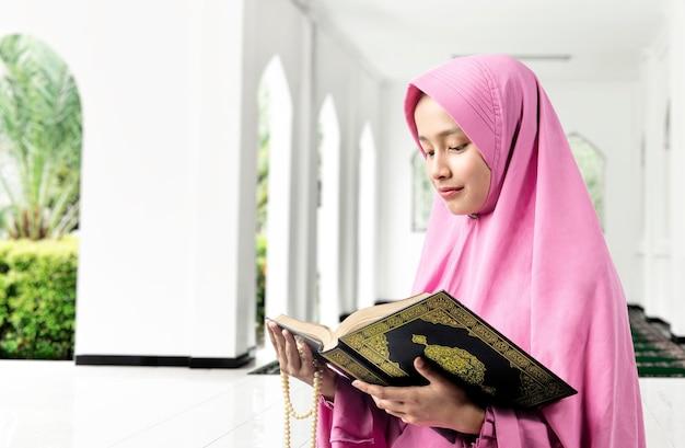 Vrouw in een sluier die gebedskralen vasthoudt en de koran leest
