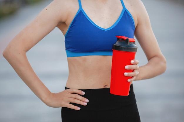 Vrouw in een sporttop met een glas sportvoeding tijdens een trainingssessie op een stadsstraat in de zomer. detailopname.