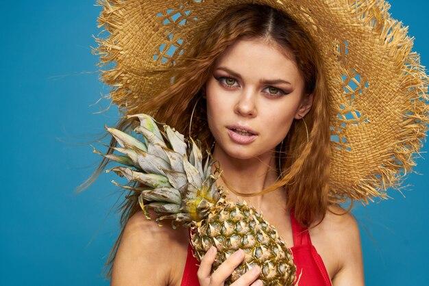Vrouw in een strooien hoed met ananas in haar handen golvend haar exotische vruchten je blauwe zomervakantie.
