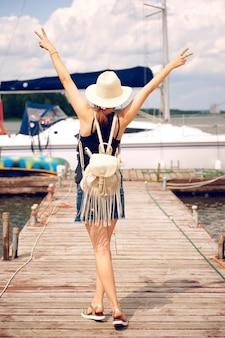 Vrouw in een strooien hoed staat in de zomer met haar rug op de pier met haar armen omhoog en toont twee vingers