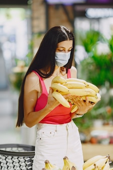 Vrouw in een supermarkt. dame in een gasmasker. meisje maakt parchases.
