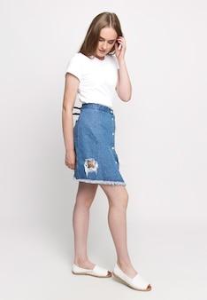 Vrouw in een t-shirt en een geïsoleerde denimrok