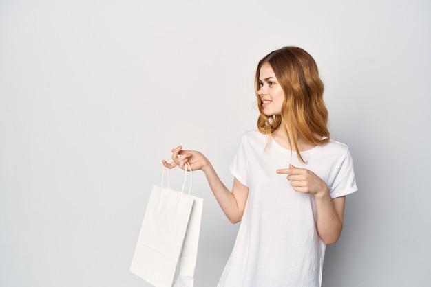 Vrouw in een t-shirtpakket in handen winkelen in de winkel