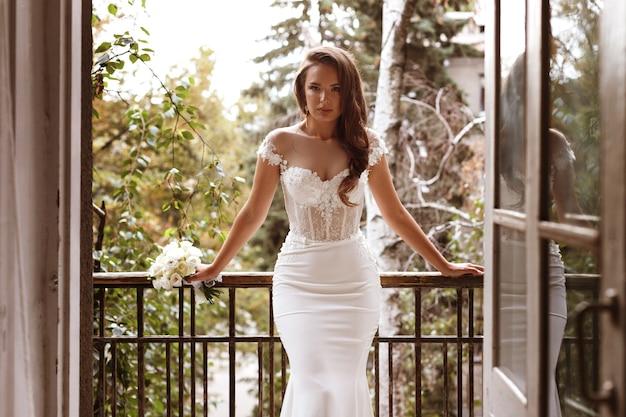 Vrouw in een trouwjurk op het balkon