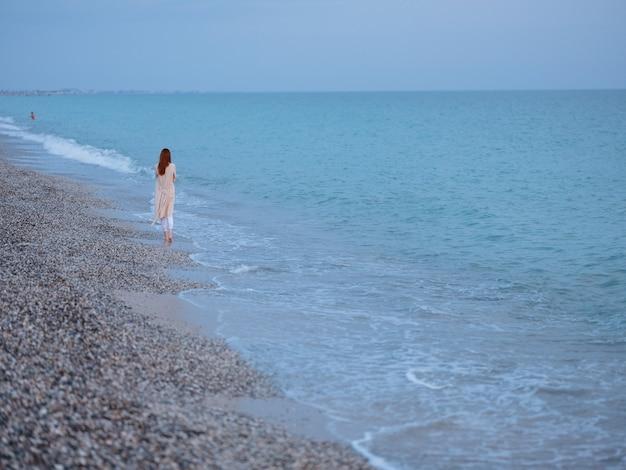 Vrouw in een trui bij de oceaan en de blauwe lucht met helder water