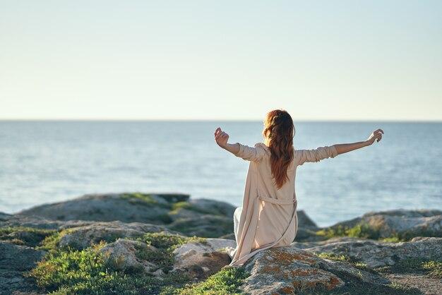 Vrouw in een trui gebaart met haar handen boven haar hoofd in de bergen in de buurt van de frisse zeelucht. hoge kwaliteit foto