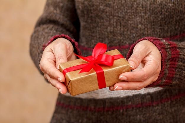 Vrouw in een trui met een geschenkdoos vastgebonden met een rood lint in haar handen. ondiepe scherptediepte, selectieve focus op de doos. concept van het geven van een cadeau op valentijnsdag of verjaardag.