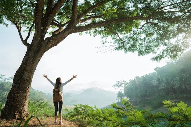 Vrouw in een vallei met veel bomen, steek handen op