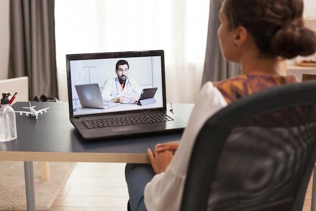 Vrouw in een videoconferentie met haar arts.