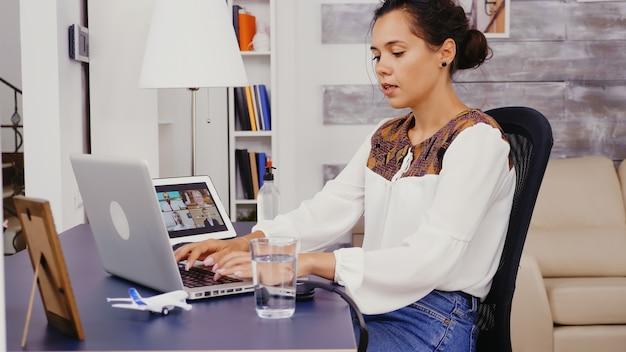 Vrouw in een videogesprek op tabletcomputer die op laptop typt terwijl ze vanuit huis werkt.