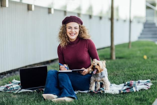 Vrouw in een violette hoed bij een picknick in het bos, naast haar op de deken een kleine hond yorkshire terrier, zonlicht, felle kleurverzadiging, eenheid met de natuur.